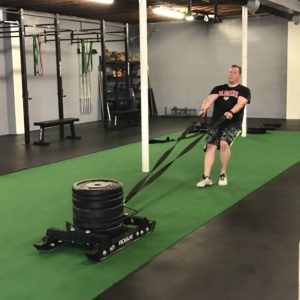 Man pulling a weighted sled