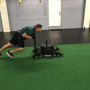 Man pushing a weight sled